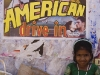 Little girl next to low budget movie poster, Kollam.