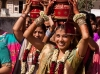 Women in the wedding carrying pots of water in a procession through the streets.
