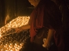 Monk lighting butter lamps at Samye Monastery.
