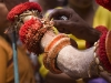 Theyyam artist plucks flower petals from his costume to give to devotees in exchange for a donation, Kannur District.