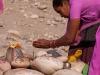 Woman worshiping at stone lingam, Kumbh Mela, Haridwar
