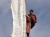 Monk hanging a prayer flag, Langmusi.
