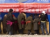Tibetan men lined up at the China Telecom cell phone tent, festival in Maqu.