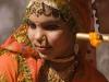 "Elaborately dressed woman ""being told a secret"" during the ""Spiritual Walk,"" Pushkar Camel Fair."