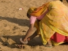 While the men tend to the camel business, the women go around gracefully picking up camel droppings to dry out and use for fule, Pushkar.