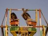 Kids enjoying a hand powered Ferris Wheel at the Pushkar Fair.
