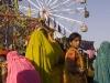 Women shopping in front of a Ferris Wheel, Pushkar Fair.