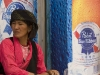 Tibetan woman sitting in front of Pabst Blue Ribbon beer adds in Shigatse.