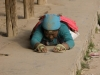 Pilgrim circumambulating Labrang monastery by prostrating and laying out her body along the entire 2 mile circut, Xiahe.