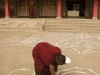 Monk drawing chalk designs prior to gathering in the main prayer hall at the Labrang monastery, Xiahe.