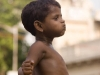 Bare-chested kid does his best Tarzan impersonation while sitting on a fence, Kailghat, Calcutta.