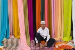 Muslim boy in front of a street side fabric shop, Hyderabad.