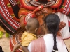 Theyyam artist blesses mother and child, in Kannur District.