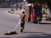 Man pulls a dead dog across the street in Srinagar, Kashmir