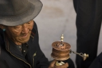 Pilgrim with a prayer wheel near the Jokhang temple, Lhasa.
