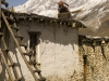 Woman sweeps snow off her roof in Muktinath.