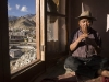 Man plays flute with view over Leh.