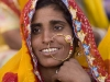 Smiling woman watching the closing ceremonies of Pushkar Camel Fair.