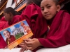 Young monk holds commemorative card displaying the new and previous Rimpoche of Spituk Monastery.