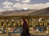 Woman turns prayer wheels in Hor Qu with Mt. Kailash in the distance.