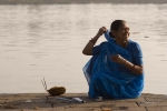 Woman performing a puja along the river, Maheshwar