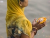 Woman sets an offering afloat in the Ganges, Varanasi.