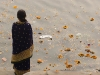 Woman starring at Ganges littered with trash from offerings as well as other matter, Varanasi.