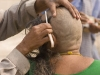 Woman having her head shaved as an offering by the Ganges, Varanasi.